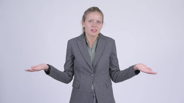 Cover Image for Young Confused Blonde Businesswoman Shrugging Shoulders