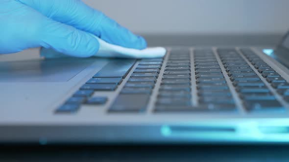 Female hand is rubbing laptop computer with sanitizer and wet wipe in office during quarantine.