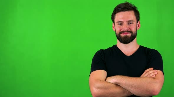 Thumbnail for Young Handsome Bearded Man Smiles To Camera with Folded Arms - Green Screen - Studio