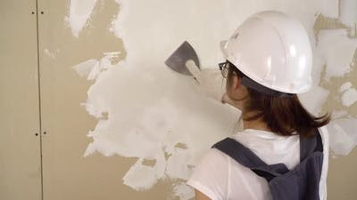 The Builder Plasters the Wall in the Room