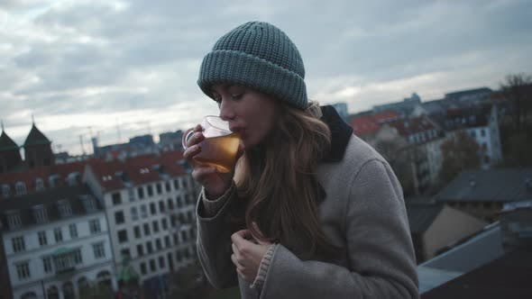 Thumbnail for Woman Looking To Camera Before Sipping Hot Drink