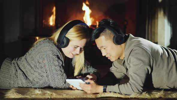 Thumbnail for Young Multi-ethnic Couple Resting By the Fireplace, Using a Tablet