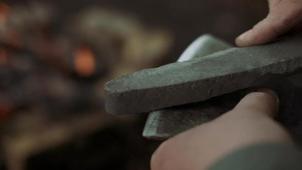 Thumbnail for Close-up Of Casual Strong Man Works with Ax and Sharpening Stone Near Warm Bonfire in Camp in Wild
