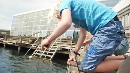 Thumbnail for Siblings By the Edge of Dock Leaning Over To Catch Crab with Strings