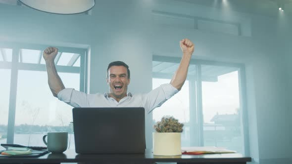 Thumbnail for Happy Business Man Getting Good News on Laptop Computer at Remote Workplace