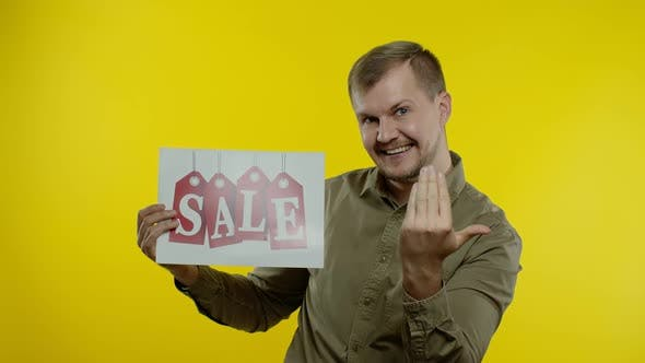 Thumbnail for Great Discounts. Happy Cheerful Blonde Man in Blue Shirt Showing Sale Word Advertisement Inscription