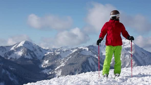 Cover Image for Skier taking in scenery and pointing to mountains with ski pole