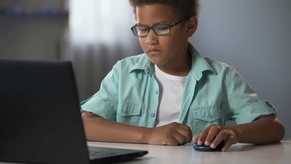 Thumbnail for Little Boy Skillfully Using Computer Mouse to Search Information on Internet