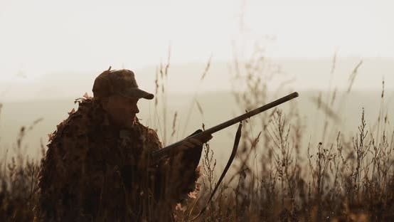 Cover Image for Hunter in hunting equipment lies in wait in field. Man in sunset light aims with rifle