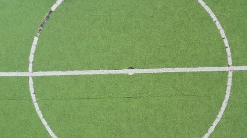 Midpoint of an artificial grass football field zooming out to reveal the field