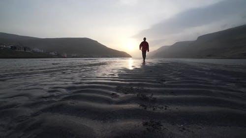 Man On Rippled Lake Sandbank At Sunrise