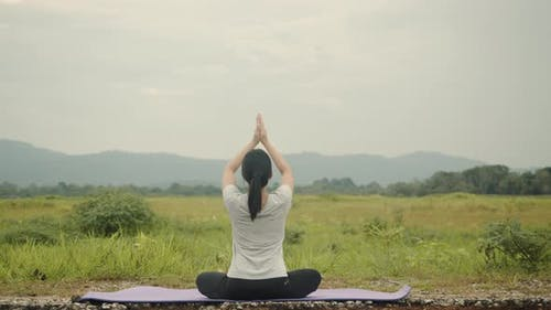 Beautiful Asian Caucasian female sitting in meditation pose position yoga pranayama balance.