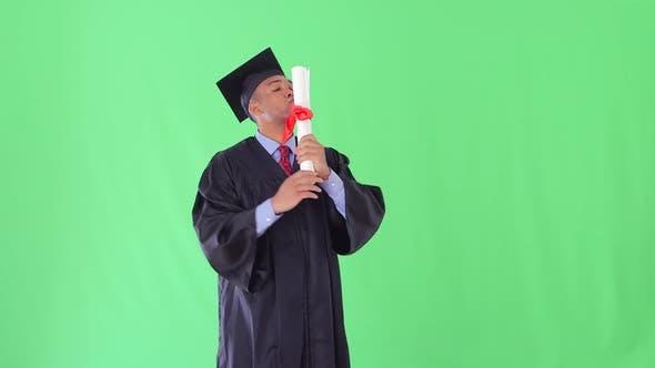 Thumbnail for Afroamerikaner Mann mit Graduierung Kleid küssen Diplom