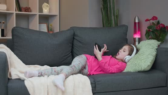 Thumbnail for Little Girl in Wireless Headphones Chilling Laughing on Sofa Listening to Favorite Music