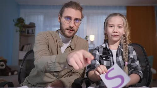 Family Looks in Laptop and Speaks at Camera in Internet Young Dad in Glasses and Girl with Cards in
