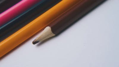 Motion Along Row of Colored Pencils on White Background