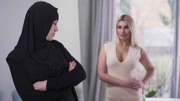 Thumbnail for Conservative Muslim Woman Looking Back at Modern Caucasian Girl in Candid Dress and Turning Away
