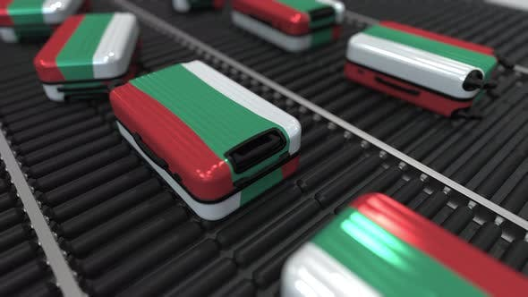 Many Travel Suitcases with Flag of Bulgaria on Conveyer
