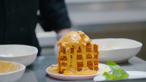 Pouring a Sweet Sauce and Granola on Honey Cake