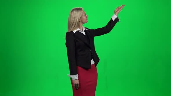 Thumbnail for Beautiful Woman Showing Something Standing Against Green Screen Chroma Key Background.