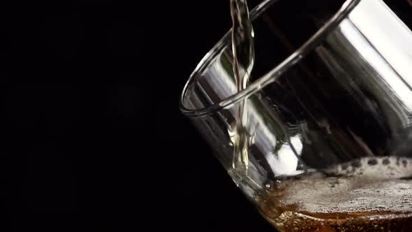 Thumbnail for Licht Bier wird langsam in ein Glas auf schwarzem Hintergrund gegossen