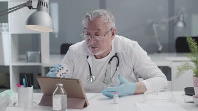 An Elderly Grayhaired Doctor Participates in a Video Conference Via the Internet on a Tablet