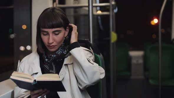 Thumbnail for Young Woman or Passenger Reading Book Sitting in Public Transport, Steadicam Shot. Slow Motion. City