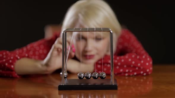 Attractive Woman Playing With A Newton's Cradle
