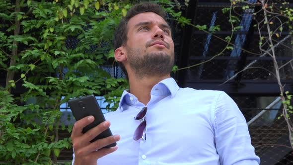 Thumbnail for A Young Handsome Businessman Stands in Front of an Office Building and Works on a Smartphone