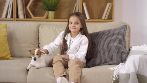 Thumbnail for Pretty Little Girl Petting Cute Dog and Smiling at Camera