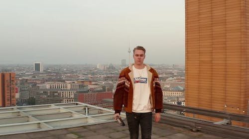 AERIAL: Confident White Caucasian Young Man, Guy Standing on Rooftop in Skyline of Berlin, Germany