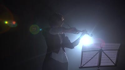 Violinist Performs on Stage with a Lantern