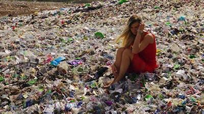 Female Nature Pollution Activist Sits at Huge Trash Dump