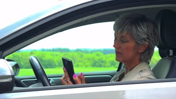 Thumbnail for Middle Aged Woman Sits in the Car and Works on the Smartphone - Car Stands on the Verge of Road