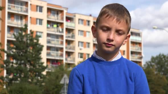 Thumbnail for A Young Boy Looks Seriously at the Camera at an Apartment Complex