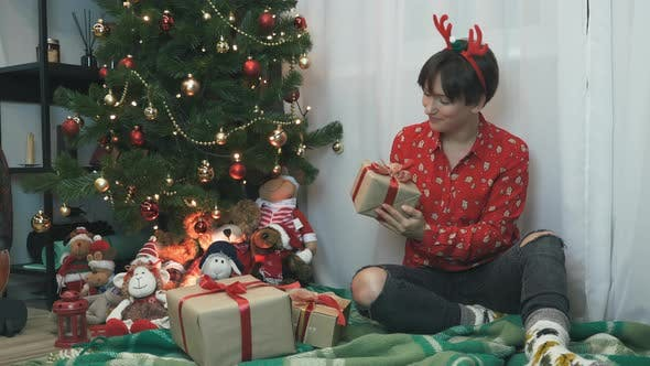 Thumbnail for Charming smiling woman is wrapping and decorating Christmas presents