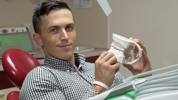 Thumbnail for Handsome Young Man Examining Dental Mold, Smiling To the Camera