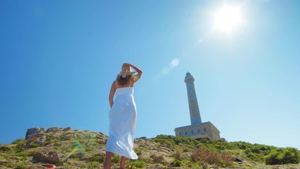 Thumbnail for A Beautiful Young Girl, Looks at an Lighthouse, in a Straw Hat. Concept: Recreation, Beautiful View