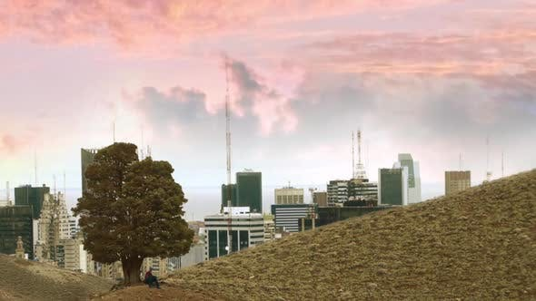 Thumbnail for City Rising over a Hill at Sunset and A Man Painting under a Tree.