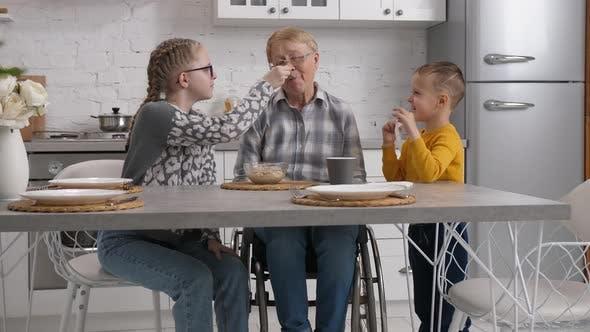 Granddaughter Feeding Breakfast To Disabled Granny