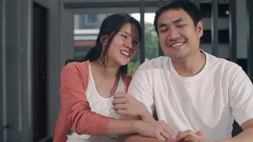 Portrait young Asian Pregnant couple smile looking to camera at home