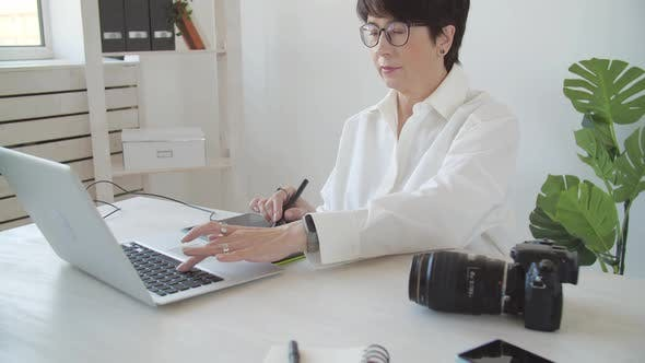 Creative Work and Hobby Concept Middleaged Woman Photo Editor Working on Computer at Her Desk with