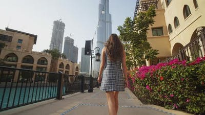 Woman Walking Through Luxury Apartment Complex Near Burj Khalifa Skyscraper in Dubai