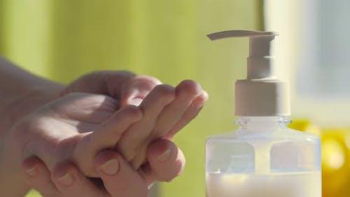 Mama behandelt die Hände ihres Babys mit einer antiseptischen oder flüssigen Seife