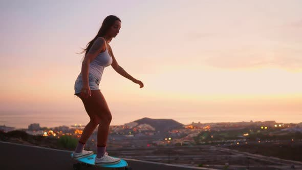 Thumbnail for Girl Riding a Skateboard Near the Ocean and a Large Mountain in Slow Motion. Healthy Lifestyle