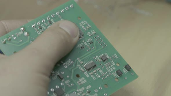 Cover Image for A Worker Is Working on the Production of an Electronic Board. Close-up.