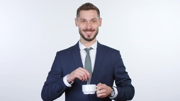 Thumbnail for Businessman Stirring Coffee and Grinning