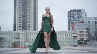 Beautiful Gorgeous Girl in a Stunning Evening Green Dress Walking Fascinatingly on Empty City Square