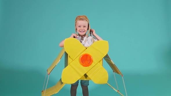 Emotional Boy in Cardboard Airplane
