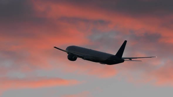Plane Flying in Evening Cloudy Sky